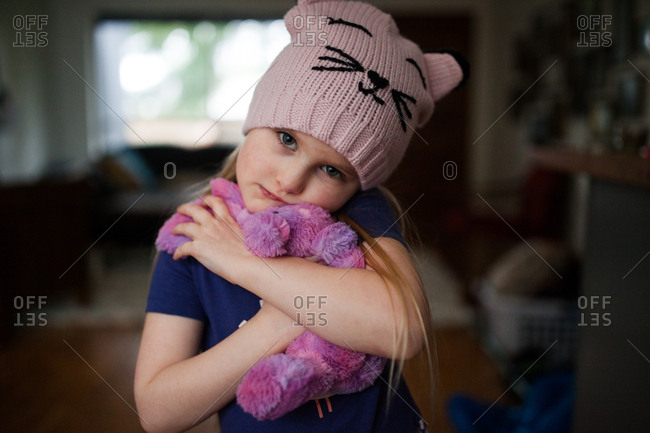Little girl wearing pink hat holding stuffed animal
