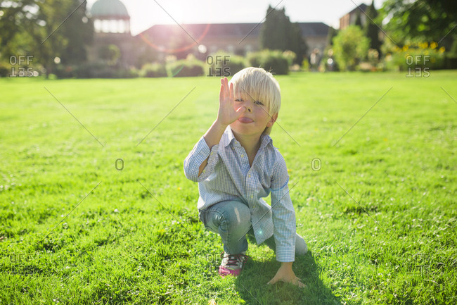 Little boy in a field making goofy faces