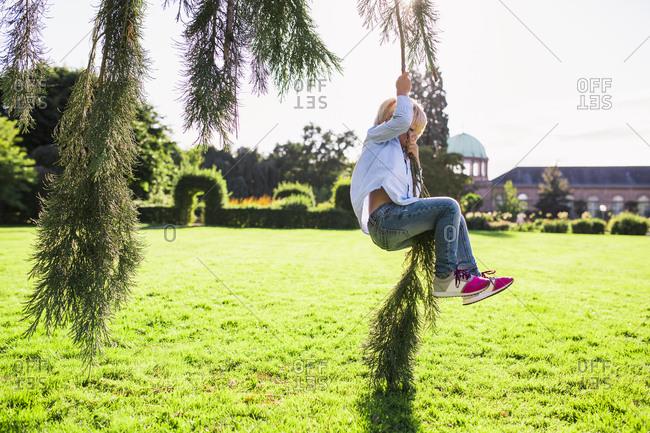 Blonde boy swinging on a tree branch