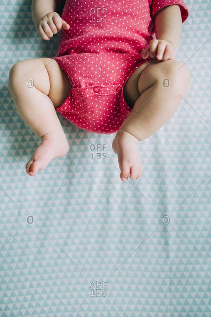 Baby's legs in a crib wearing a pink bodysuit