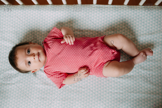 Three-month-old baby girl lying in a crib wearing a pink bodysuit
