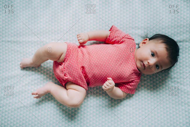 Three-month-old baby girl lying in a crib wearing a pink bodysuit with polka dots