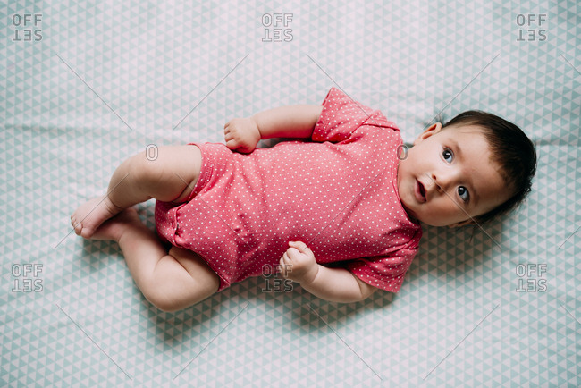High angle view of baby girl lying in a crib wearing a pink bodysuit with polka dots