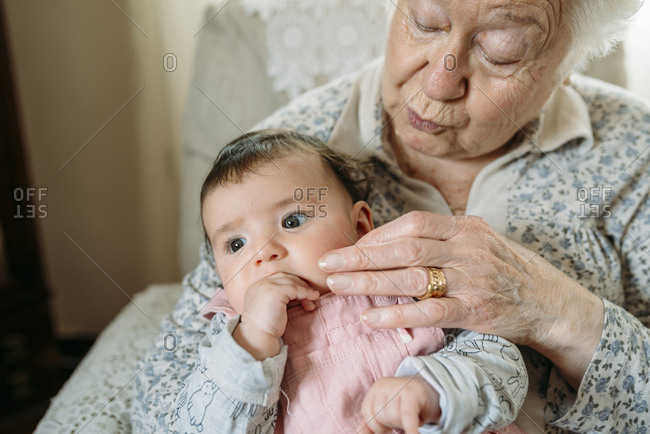 Great grandmother taking care of her great granddaughter