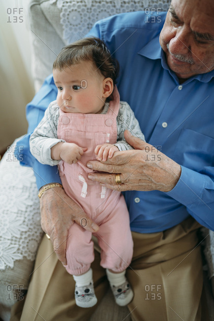 Great grandfather taking care of his great granddaughter