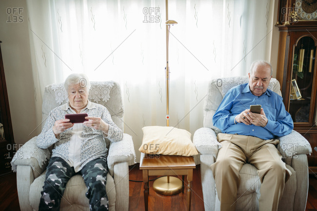 Elderly couple using smartphones