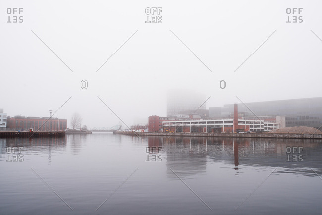 Malmo, Sweden - March 28, 2017: Foggy sky over city buildings and river