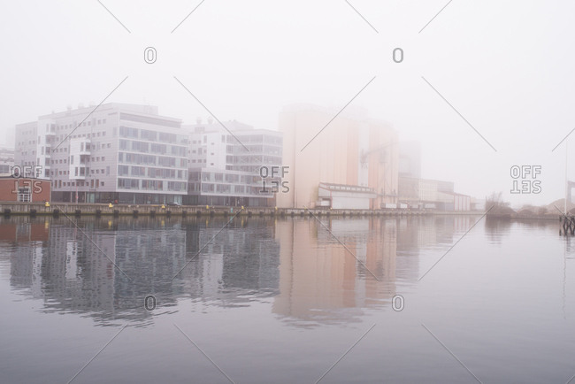 Malmo, Sweden - March 28, 2017: Buildings reflecting in water under foggy sky