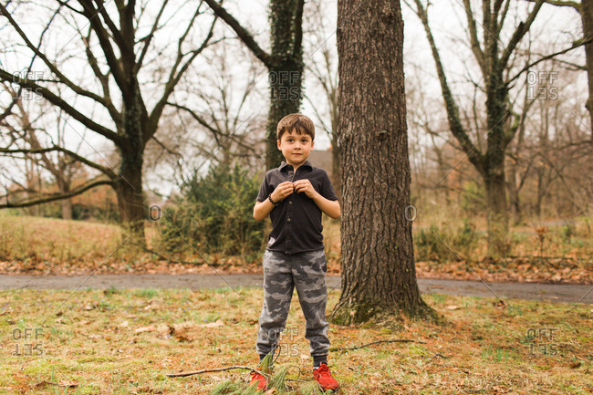 Little boy standing outside near tree