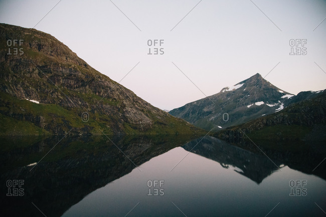 Peaks of mountains reflected in lake