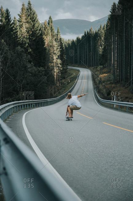 Man skateboarding down mountain road