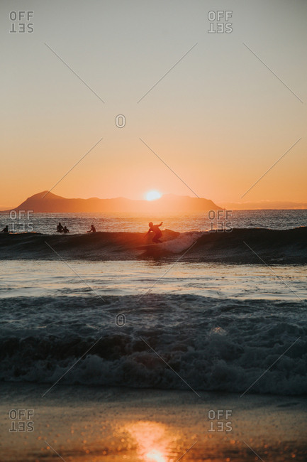 People surfing in setting sun