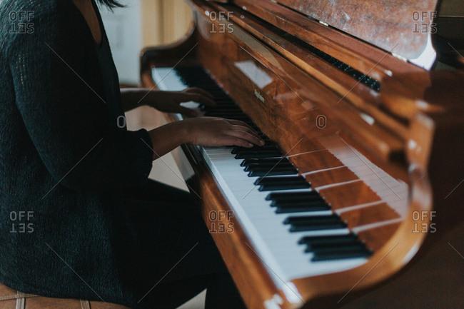 Woman sitting playing piano