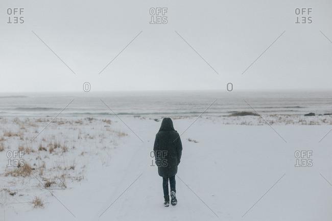 Person walking snowy field alone