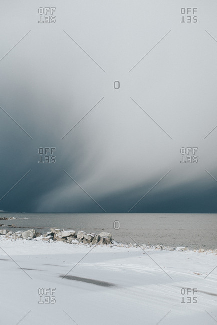 Cloudy skies over snowy shore