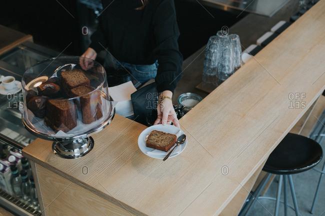 Hip barista serving bread