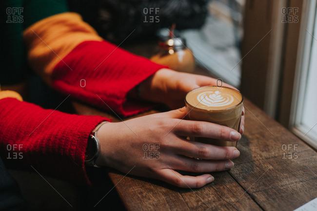 Person holding coffee mug by window