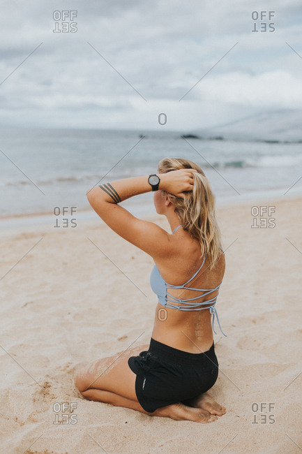 Woman sitting in beach sand, Hawaii