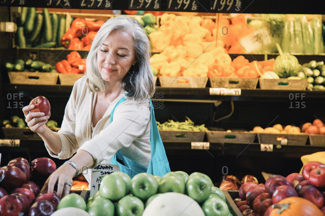Mature woman smiling while buying apples at supermarket