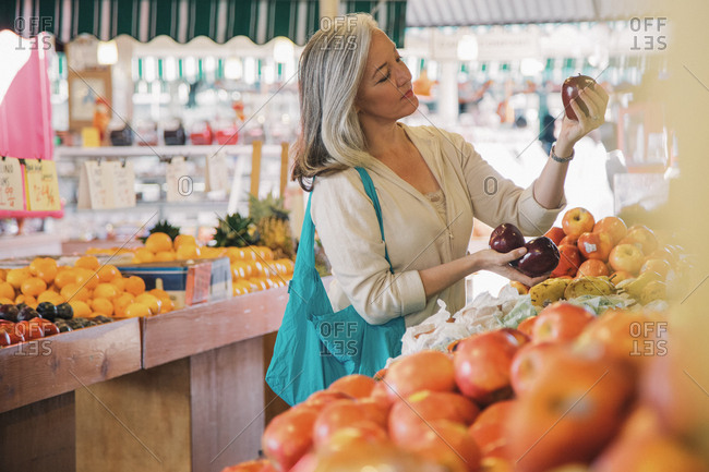 Mature woman examining apples while shopping in supermarket