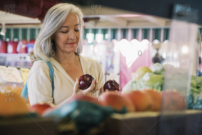 Mature woman buying apples in supermarket