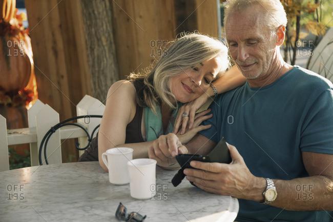 Loving mature couple using smart phone together at sidewalk cafe