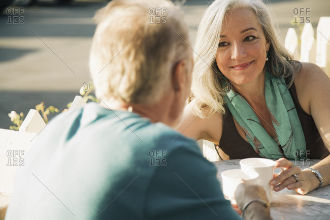 Smiling mature woman looking at man while sitting at sidewalk cafe during sunny day