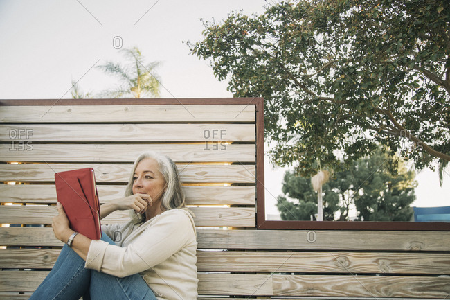 Mature woman using digital tablet while sitting on wooden bench at sidewalk cafe