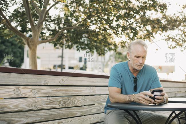 Mature man using smart phone while sitting at sidewalk cafe