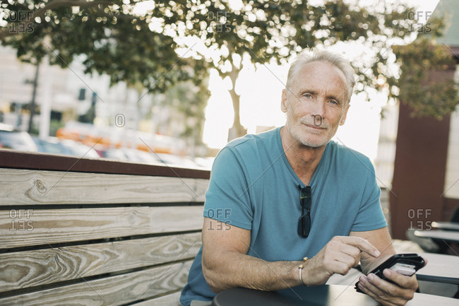 Portrait of confident mature man holding smart phone while sitting at sidewalk cafe