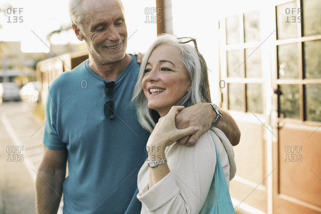 Loving mature man looking at woman while standing on sidewalk
