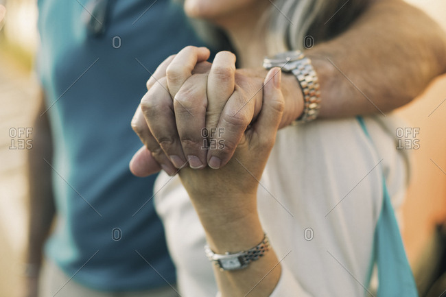 Close-up of mature couple holding hands while standing outdoors