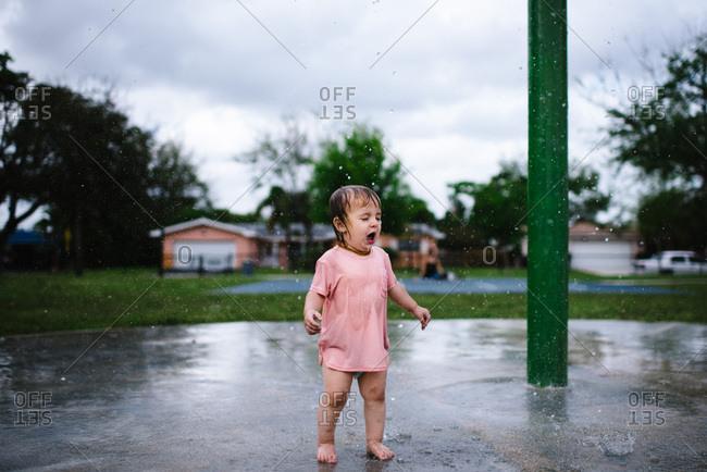Toddler girl in pink shirt standing under a sprinkler in a park.