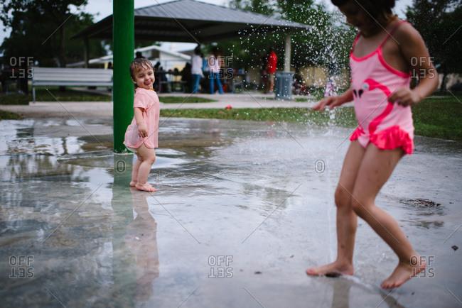 Sisters playing at a splash pad.
