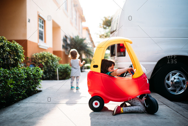 Young girl sitting in a plastic toy car outside having fun.