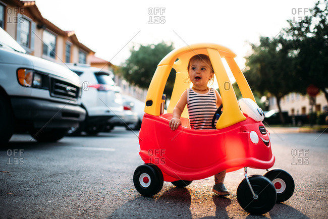 Toddler girl playing in a plastic toy car outside in pretty light.
