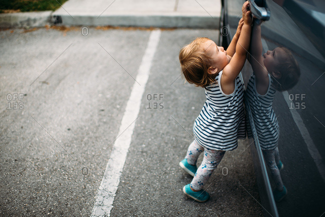 Toddler girl reaching to try to open van door.
