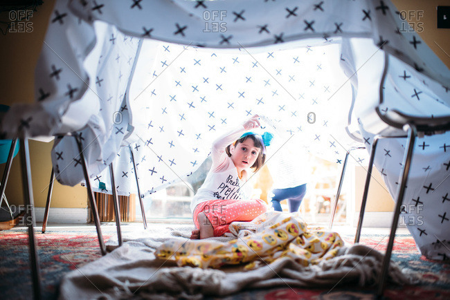 Young girl alone in a fort made out of blankets.