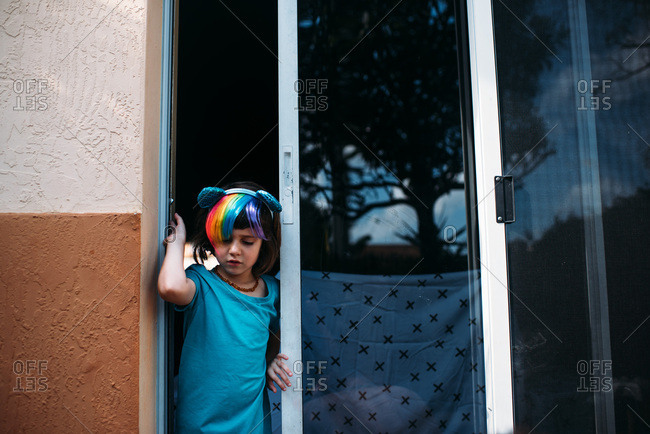 Young girl wearing a rainbow headband in the opening of a sliding glass door.