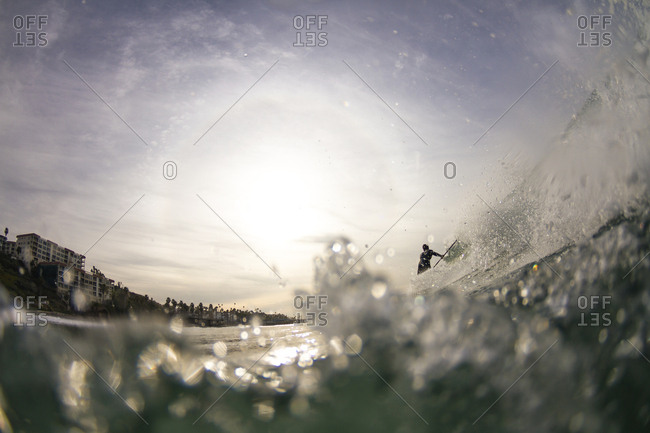 Water shot of a paddle surfer riding a wave in San Clemente, California.