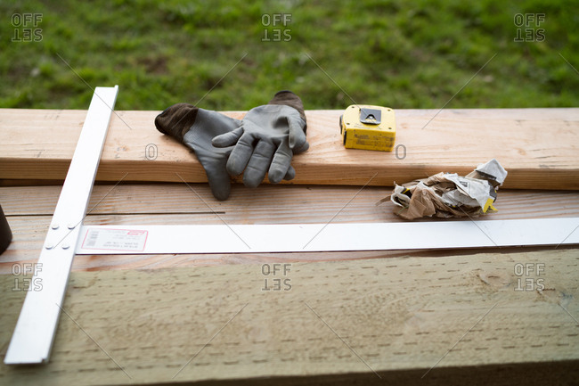 Gloves, T-square, and tape measure resting on lumber