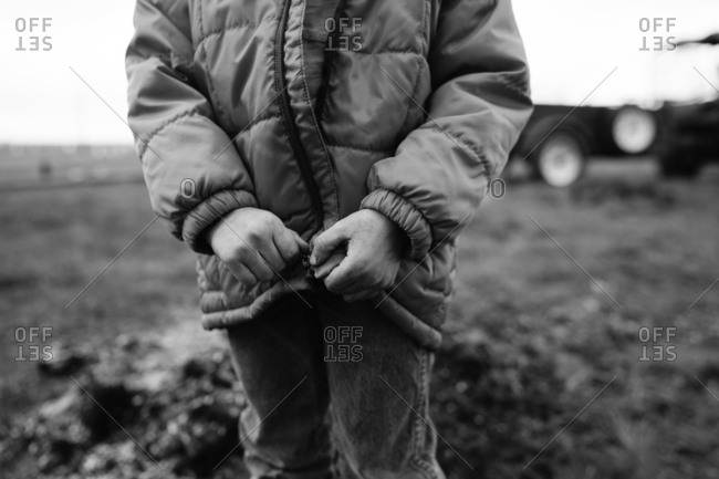 Close-up of child's hands zipping coat
