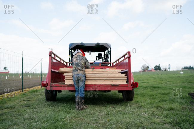 Back view of boy resting on lumber in cart