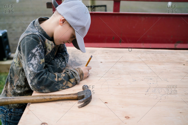 Boy writing on plywood with pencil