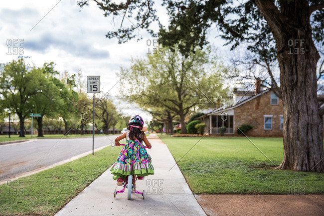 Girl riding bicycle on sidewalk