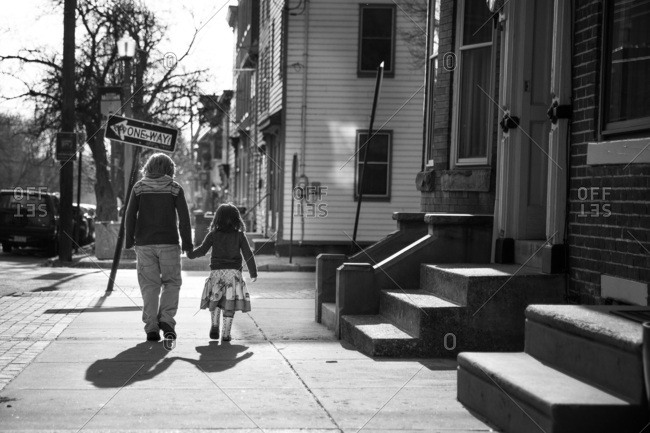 Young children holding hands while walking on sidewalk in urban neighborhood