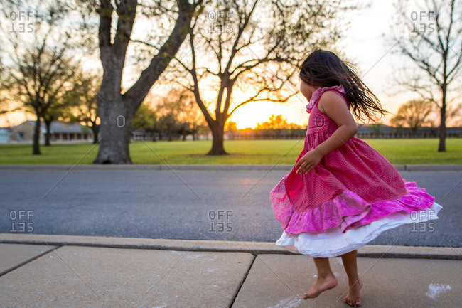 Girl dancing and twirling at sunset