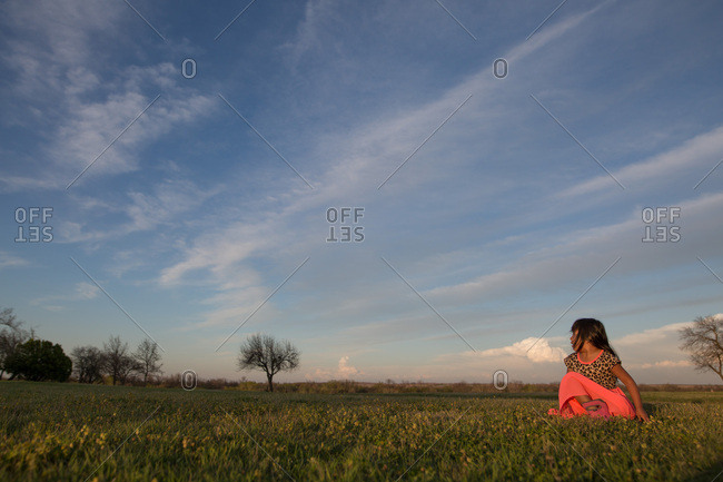 Young girl in field with big sky behind her