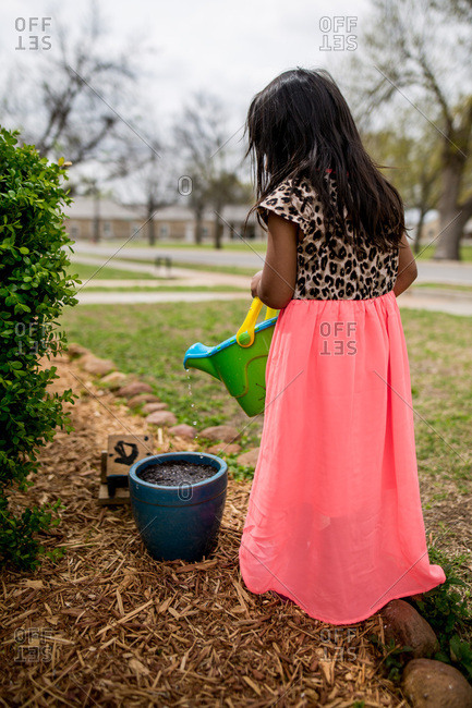Girl in dress watering plant pot
