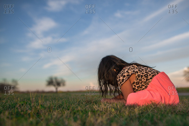 Young girl sitting in field examining grass